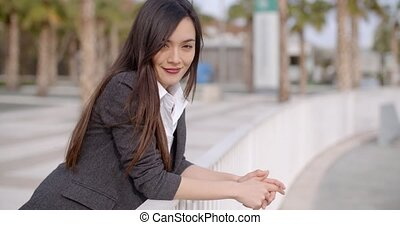 Relaxed thoughtful young woman leaning on railings - Relaxed...