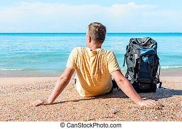 relaxed tourist with a backpack near the sea on the beach