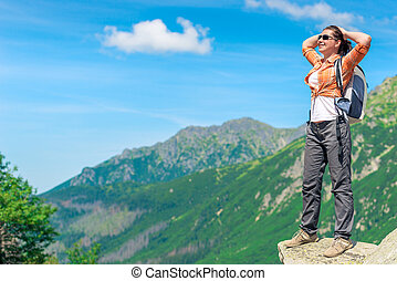 relaxed tourist with a backpack on the background of beautiful scenery in the mountains