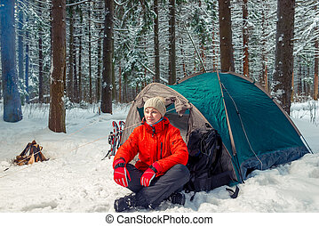 relaxed tourist woman sitting near a tent in a winter forest