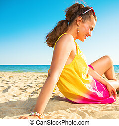 relaxed trendy woman sitting in colorful dress on beach