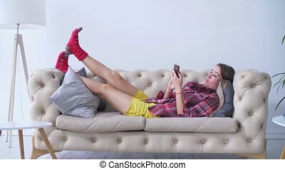 Relaxed woman checking her cellphone on couch - Relaxed...