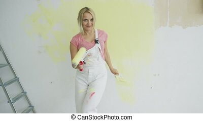 Relaxed woman dancing with paint roller
