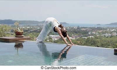 Adult female with closed eyes stretching body in sphinx pose. while practicing yoga alone poolside against resort town and seascape