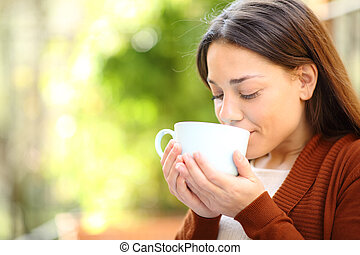 Relaxed woman drinking coffee in a garden