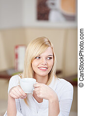 relaxed woman holding a cup of coffee