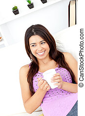 Relaxed woman holding a cup of coffee sitting on the sofa