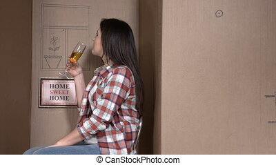 woman in a cardboard box celebrating with champagne moving into a new tiny house