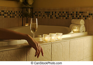 Relaxed Woman in bubble bath with sparkling wine and candles surrounding her.