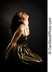 Relaxed woman in gold evening dress on black
