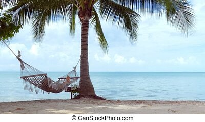 Relaxed woman lying in hammock on the beach