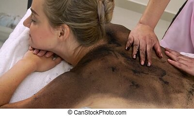 Relaxed young woman lying on spa bed for body scrubbing massage using traditional herbs and spices by massage therapist in a luxury spa resort. Wellness, stress relief and rejuvenation concept.
