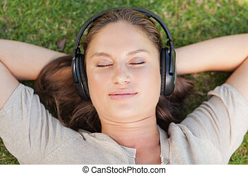 Relaxed woman lying on the lawn while listening to music