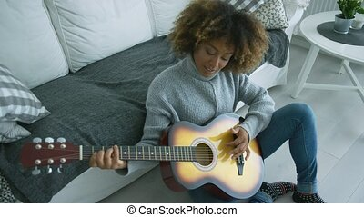 Relaxed woman playing guitar at home - Ethnic young model...