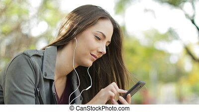 Relaxed woman putting earbuds and listening to music