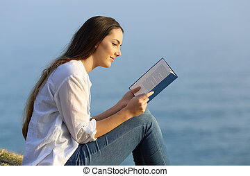 Relaxed woman reading a book sitting on the beach