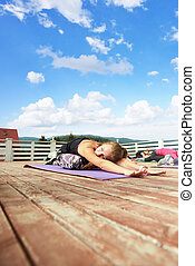 Relaxed woman sitting in child's pose during yoga class.