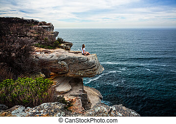 Relaxed woman sitting on coastal headland looking out to ocean