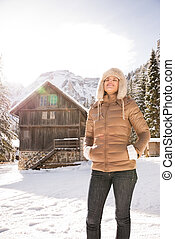 Relaxed woman standing in the front of a cosy mountain house...