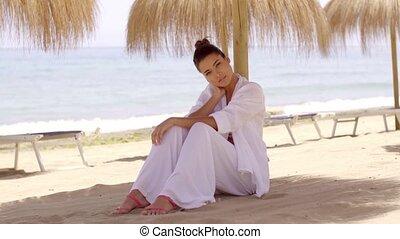 Relaxed woman under shade umbrella at beach - Single cute...