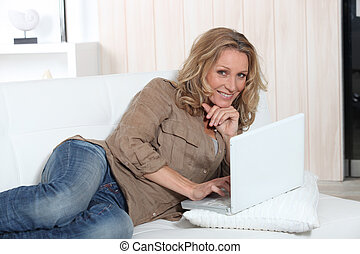 Relaxed woman using a laptop computer on her sofa