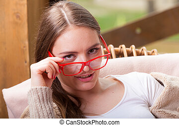 Relaxed woman wearing red glasses sitting on chair