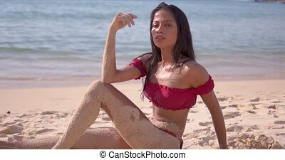 Relaxed woman with sandy legs sitting on beach - Side view ...