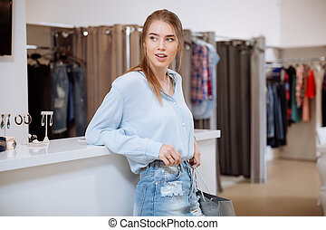 Relaxed woman with shopping bag standing in clothing store