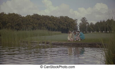 Relaxed women feeding fishes in park pond