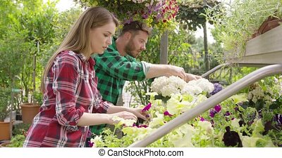 Relaxed workers with flowers in garden