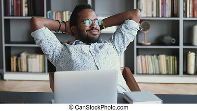 Relaxed young african businessman rest sit at work desk - ...