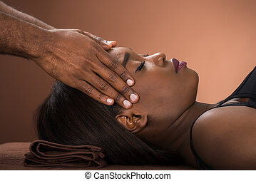 Woman Receiving Forehead Massage In Spa