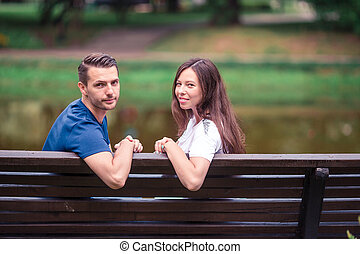 Relaxed young family on the bench in the park