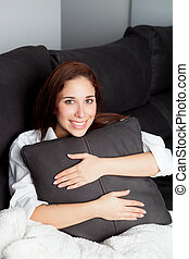 Relaxed young girl hugging a cushion
