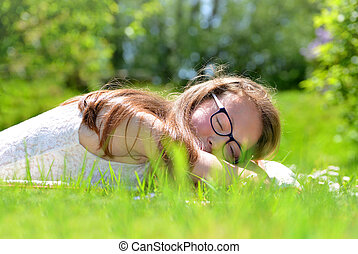 Relaxed young girl lying in grass.