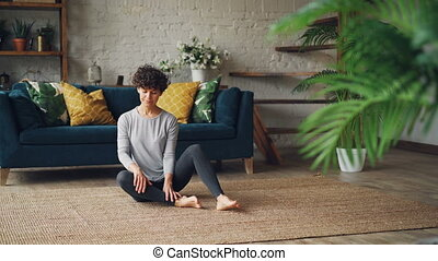 Relaxed young lady is sitting in Fire Log Pose Agnistambhasana on apartment floor and breathing in and out during yoga practice at home. Millennials, hobby and sports concept.