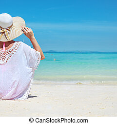 Relaxed young lady looking at the calm ocean