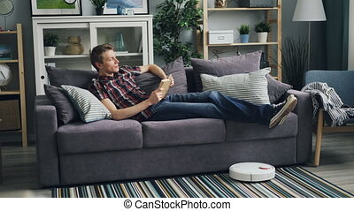 Relaxed young man is reading book at home enjoying modern...