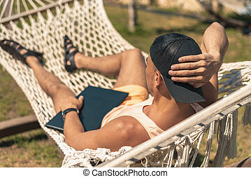 Relaxed young man lying in hammock with laptop, remote work,...