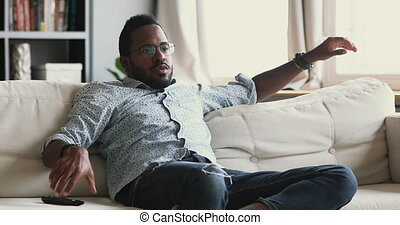 Relaxed young mixed race guy switching channels with remote ...