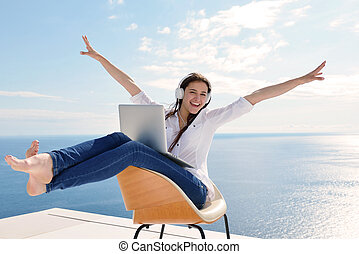 relaxed young woman at home working on laptop - beautiful ...
