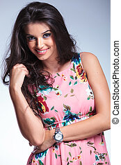 relaxed young woman in casual floral dress smiles