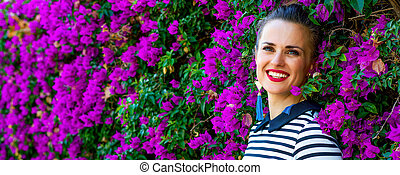 relaxed young woman in front of colorful magenta flowers bed...