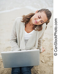 Relaxed young woman in sweater sitting on lonely beach with laptop