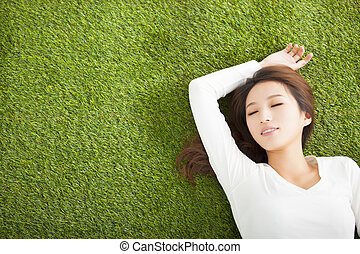 Relaxed young woman  lying on the grass