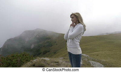 Relaxed young woman peacefully admiring the nature standing...