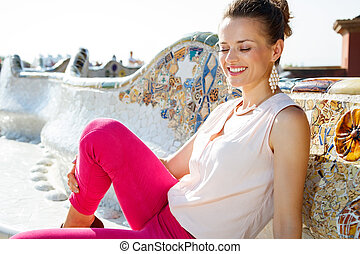 Relaxed young woman sitting on the famous trencadis style bench