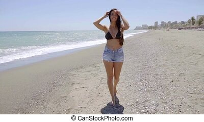Relaxed young woman walking along a sandy beach