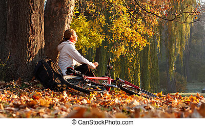 Relaxes woman cyclist with bike sits among fallen leaves ...