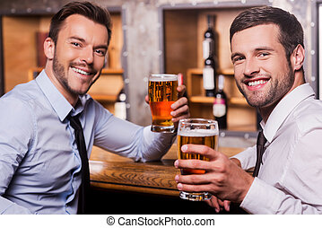 Relaxing after hard working day. Two happy young men in shirt and tie holding glasses with beer and smiling while sitting at the bar counter